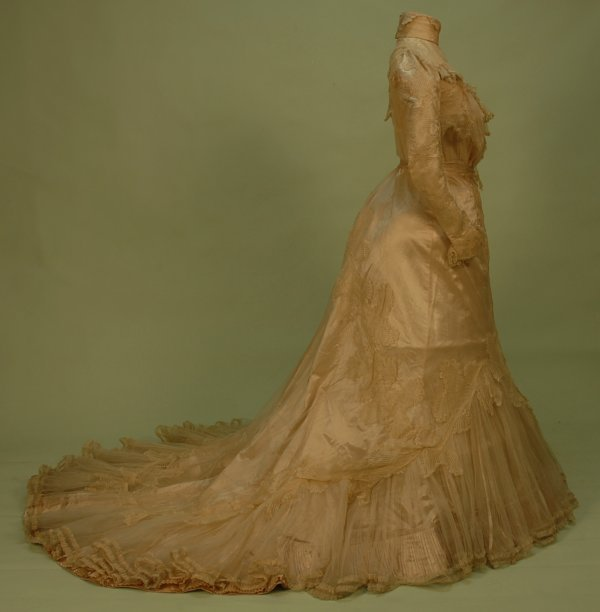329: TRAINED CREAM SILK and LACE EVENING GOWN, 1870's.