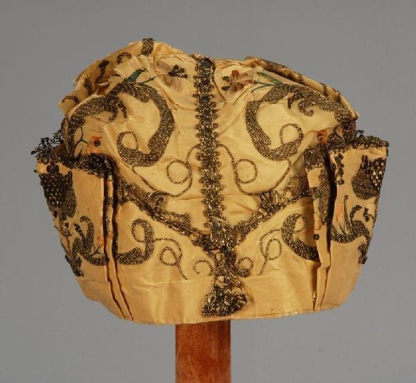 573: METALLIC EMBROIDERED SILK BABY CAP, 18th C. Cream