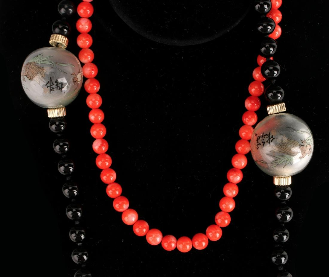 TWO NECKLACES OF CORAL AND ONYX