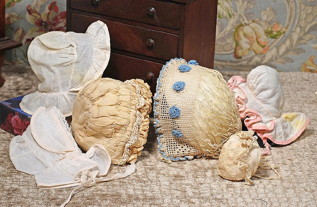 FIVE DOLL BONNETS Crocheted ivory bonnet with blue