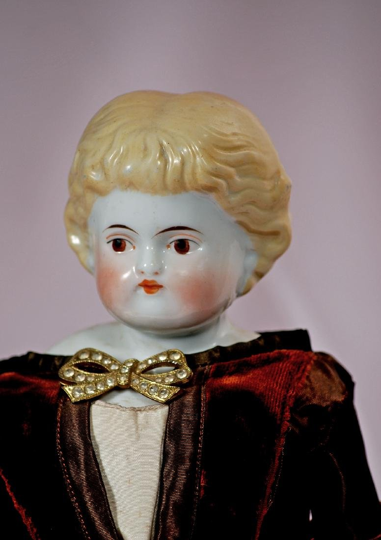 "42. GERMAN PORCELAIN DOLL WITH BROWN EYES. 18""."
