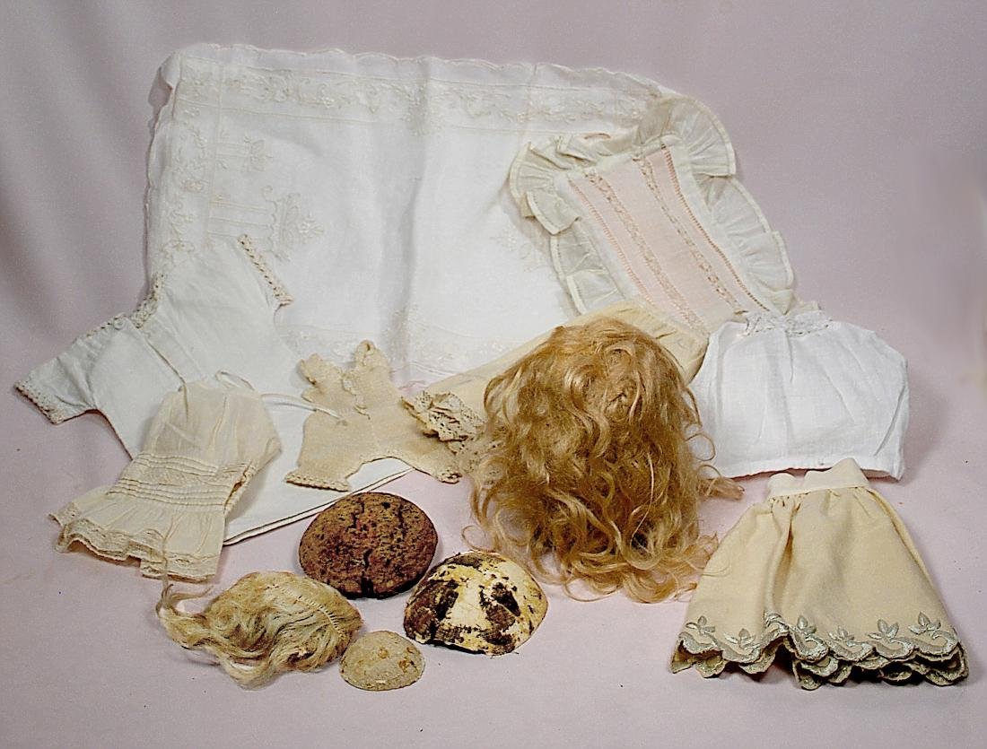 251. ANTIQUE DOLL WIGS AND UNDER GARMENTS. Six pieces