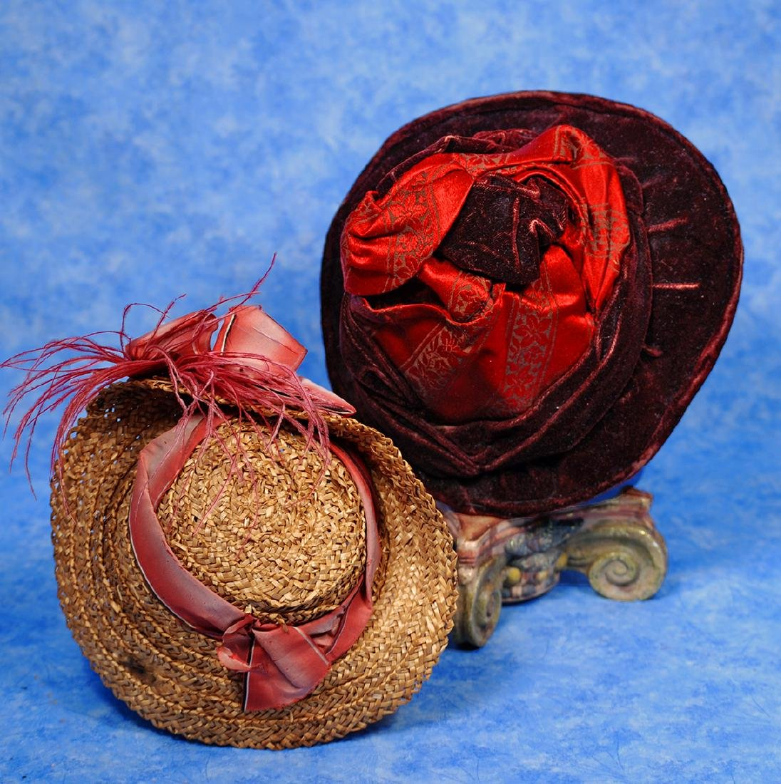 40. TWO ANTIQUE DOLL BONNETS. (1) Woven straw bonnet