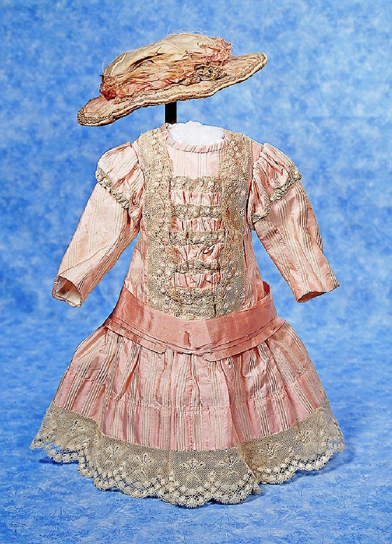 54. PINK SILK DOLL DRESS AND BONNET. Pink and cream