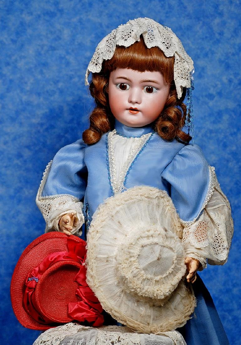 189. TWO DOLL BONNETS. Red woven straw bonnet with