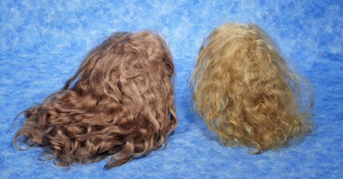 234. TWO DOLL WIGS. Antique light brown mohair wig,