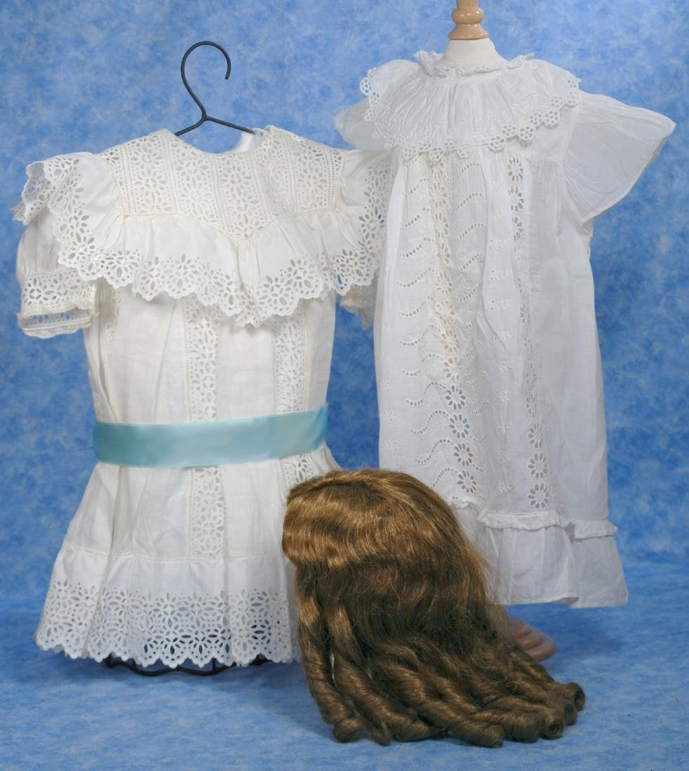 235. DOLL WIG & TWO WHITE COTTON DOLL DRESSES. (1)Brown