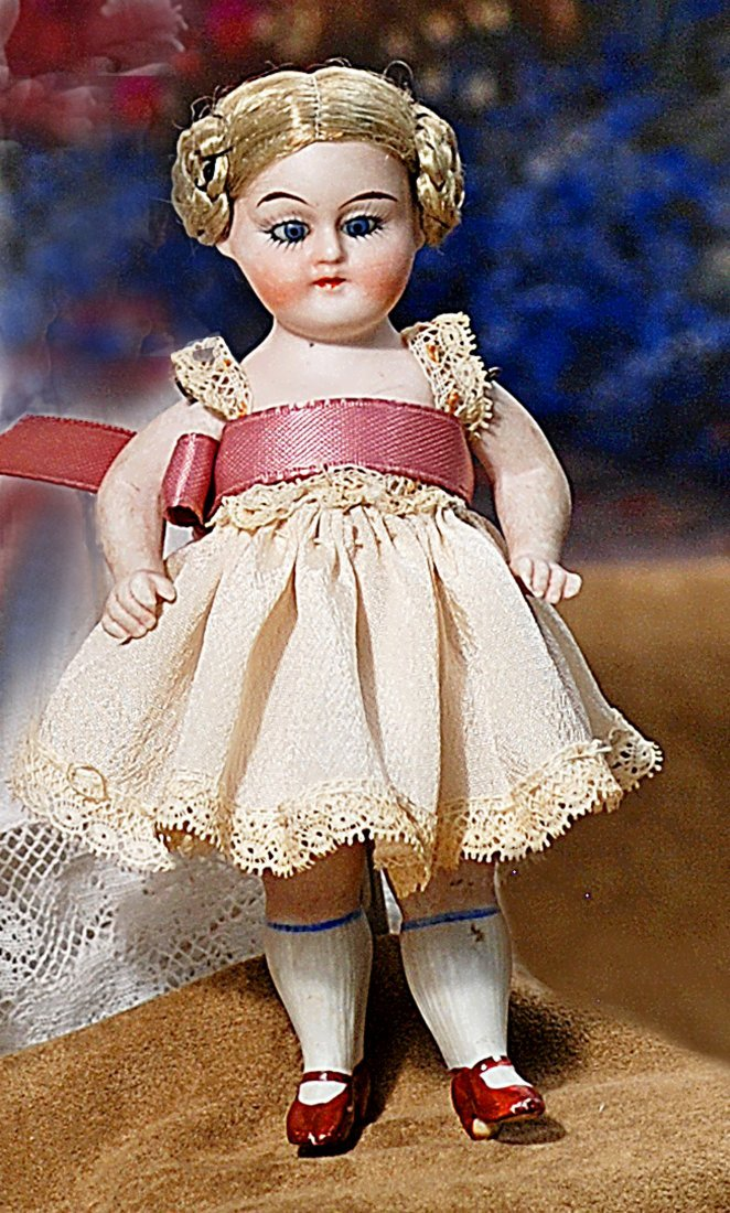 TINY GERMAN ALL-BISQUE DOLL WITH GLASS EYES.
