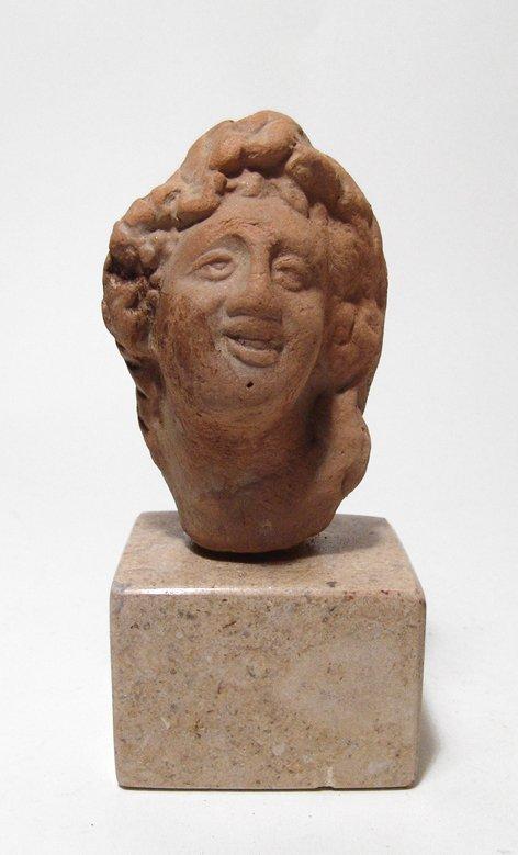 A Roman terracotta head of a cheerful youth