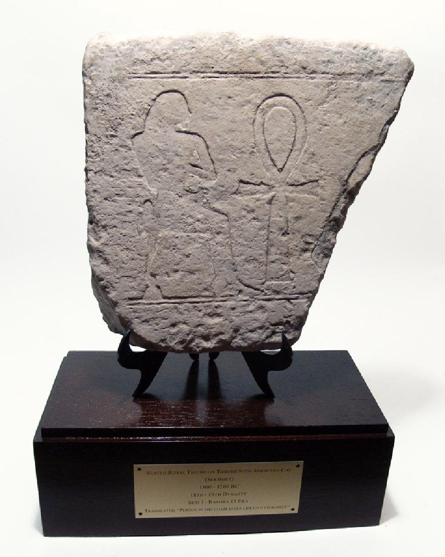 Egyptian limestone relief depicting seated royal figure