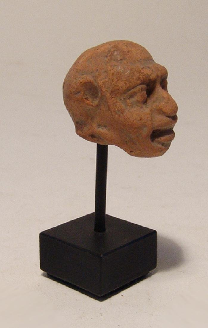 A Greek terracotta head of a grotesque
