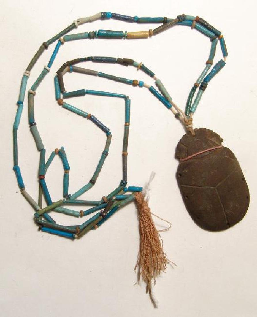 A strand of Egyptian faience beads with scarab pendant
