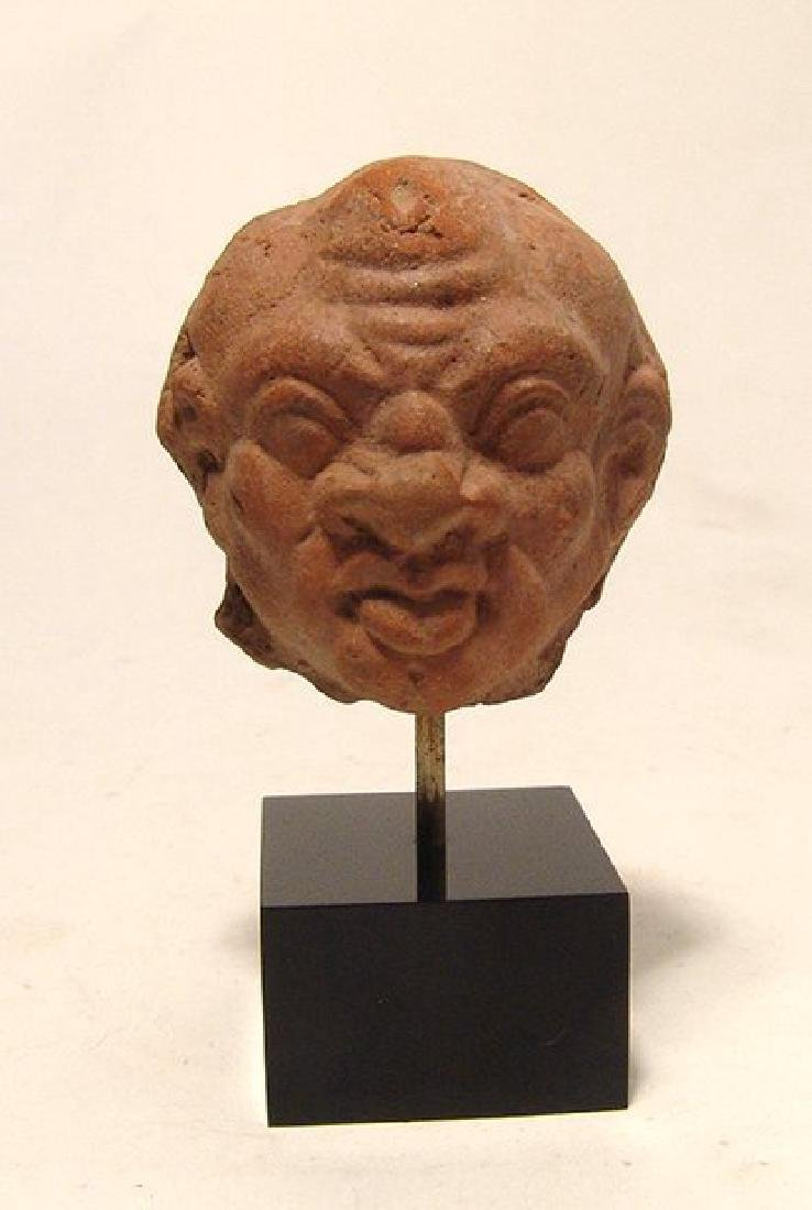 A Greek ceramic head of a male grotesque