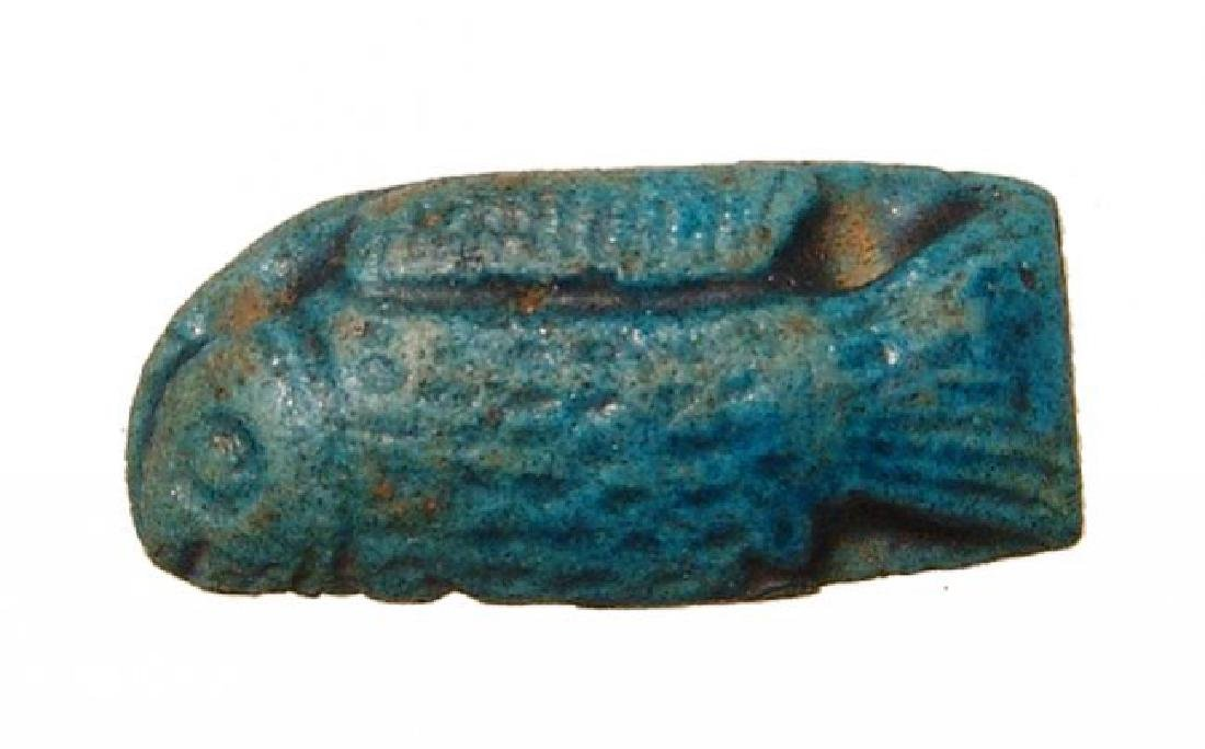 An Egyptian blue glazed amulet of a fish, Ptolemaic