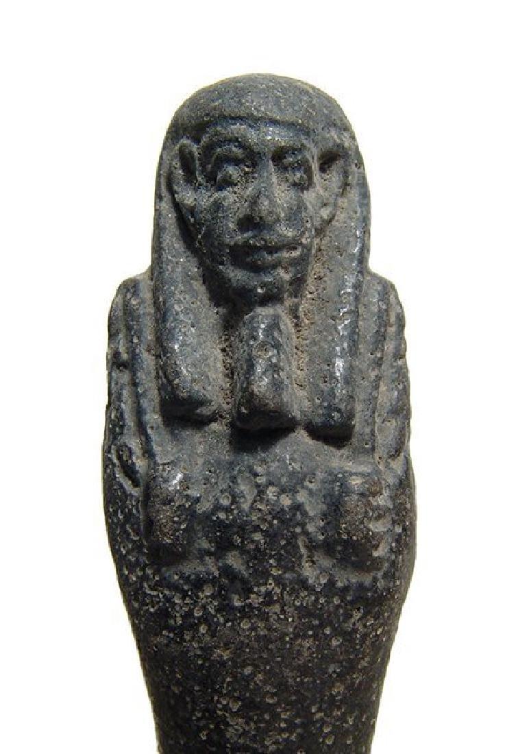 An Egyptian faience ushabti with black glaze, Late - 2