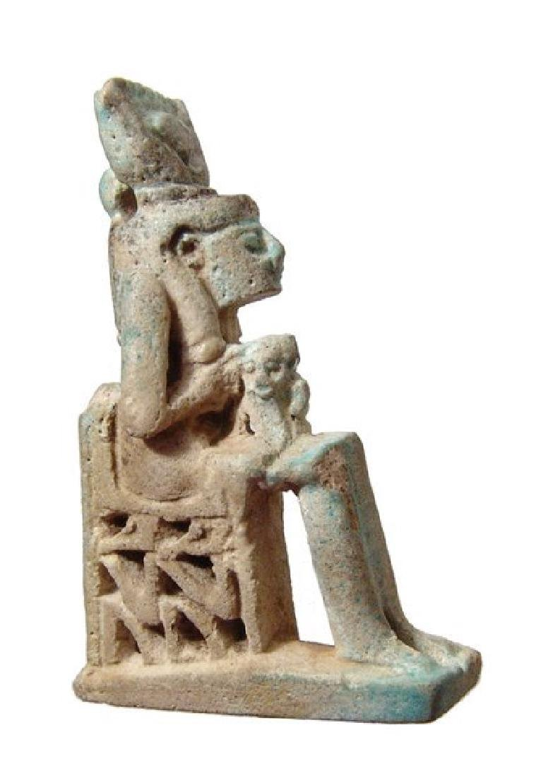 An Egyptian faience amulet of Isis holding child Horus