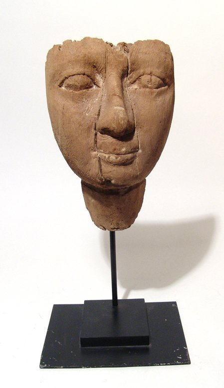 An Egyptian wooden mummy mask with naturalistic detail