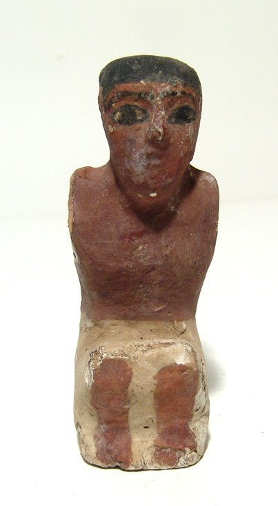 An Egyptian seated wood painted figure of a man