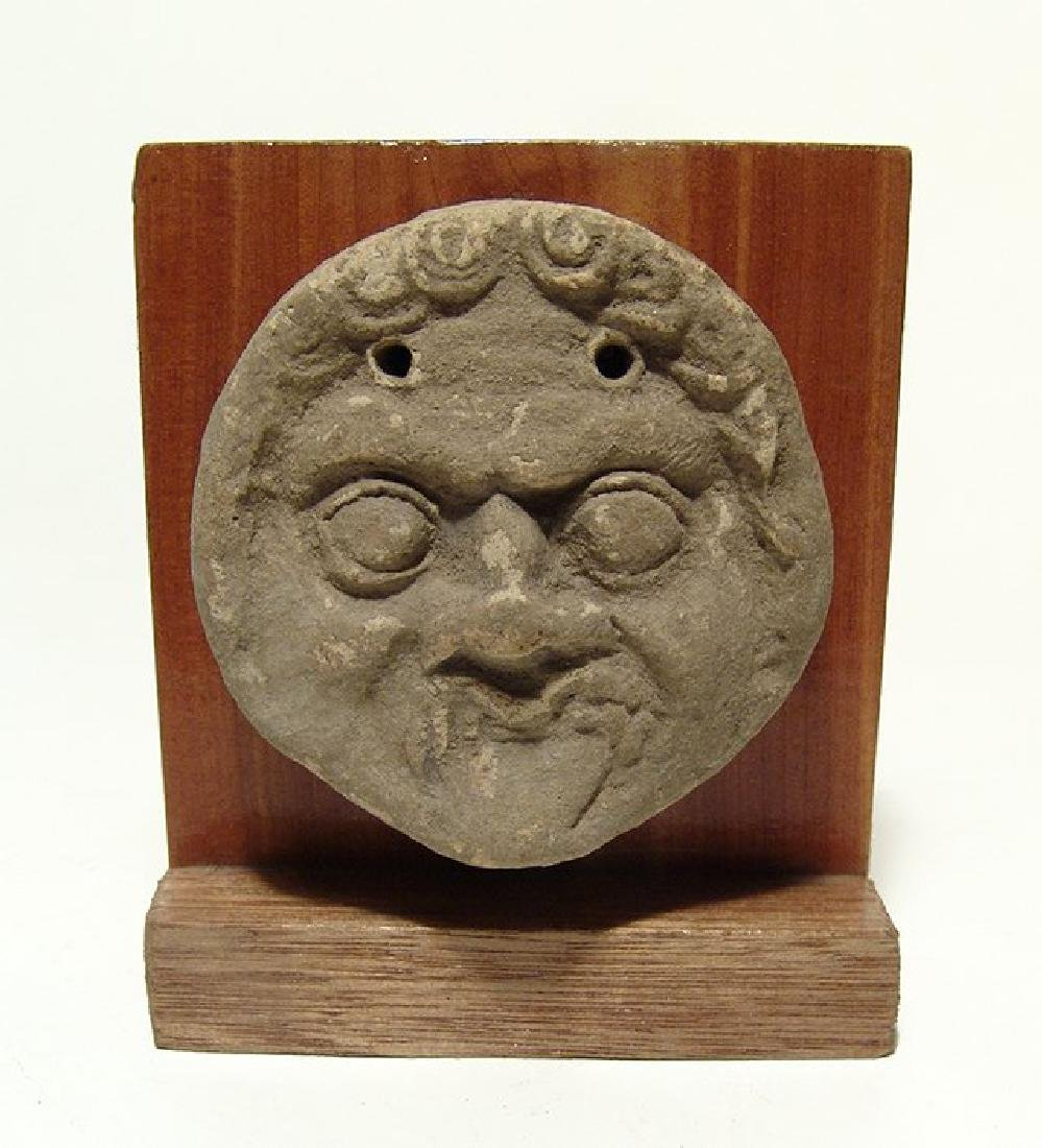 A Greek terracotta antefix depicting the face of a