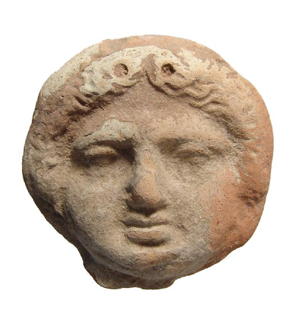 Greek terracotta roundel depicting the face of a Gorgon