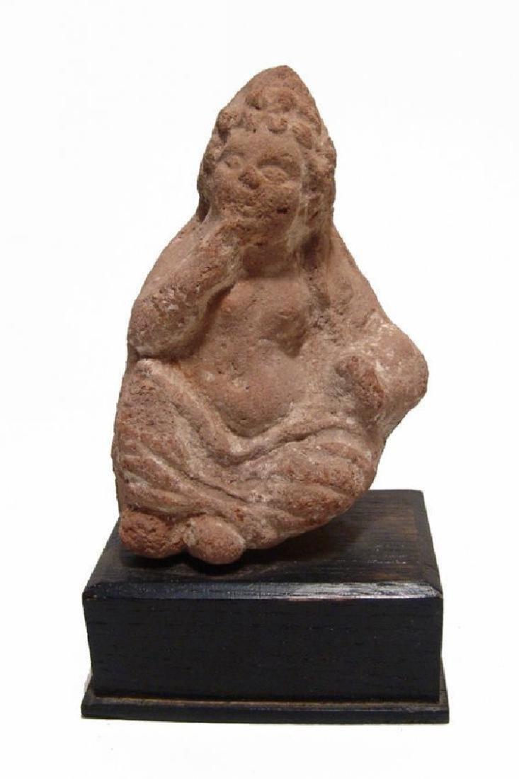 A Greek terracotta figure of a seated Harpokrates