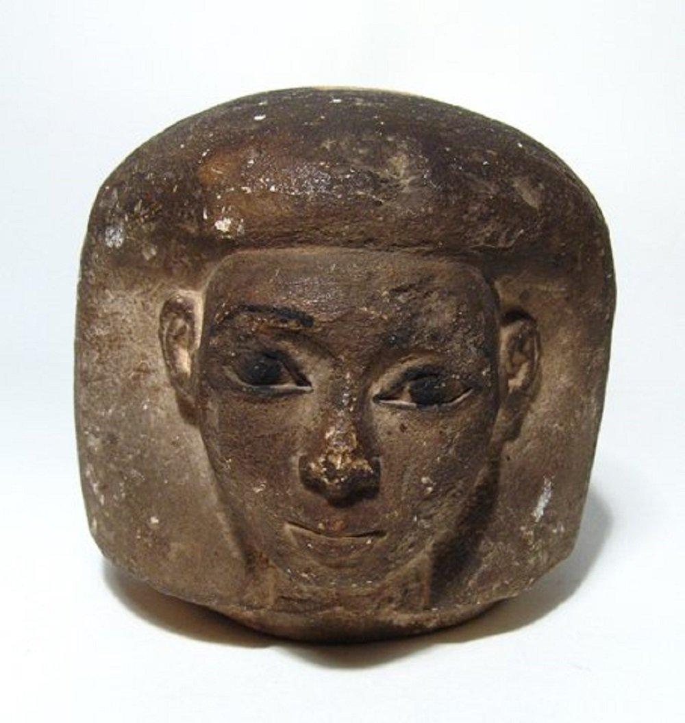 An Egyptian limestone canopic jar head of Imsety