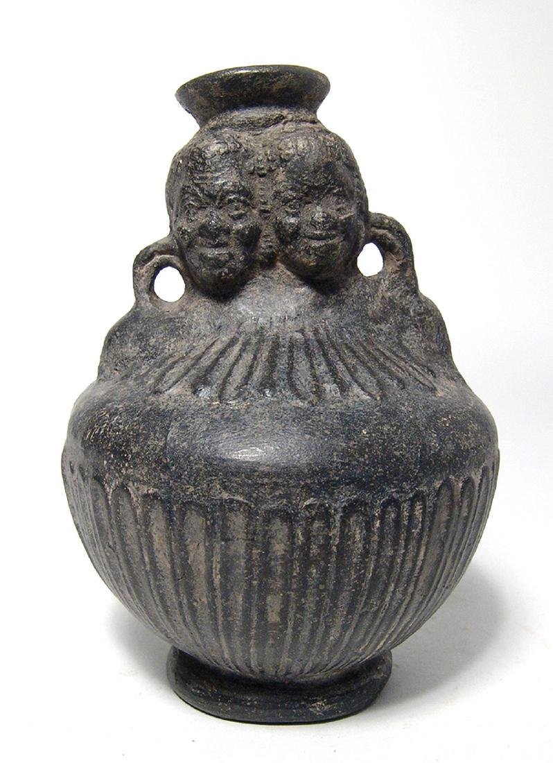 A Roman molded jug with two African heads