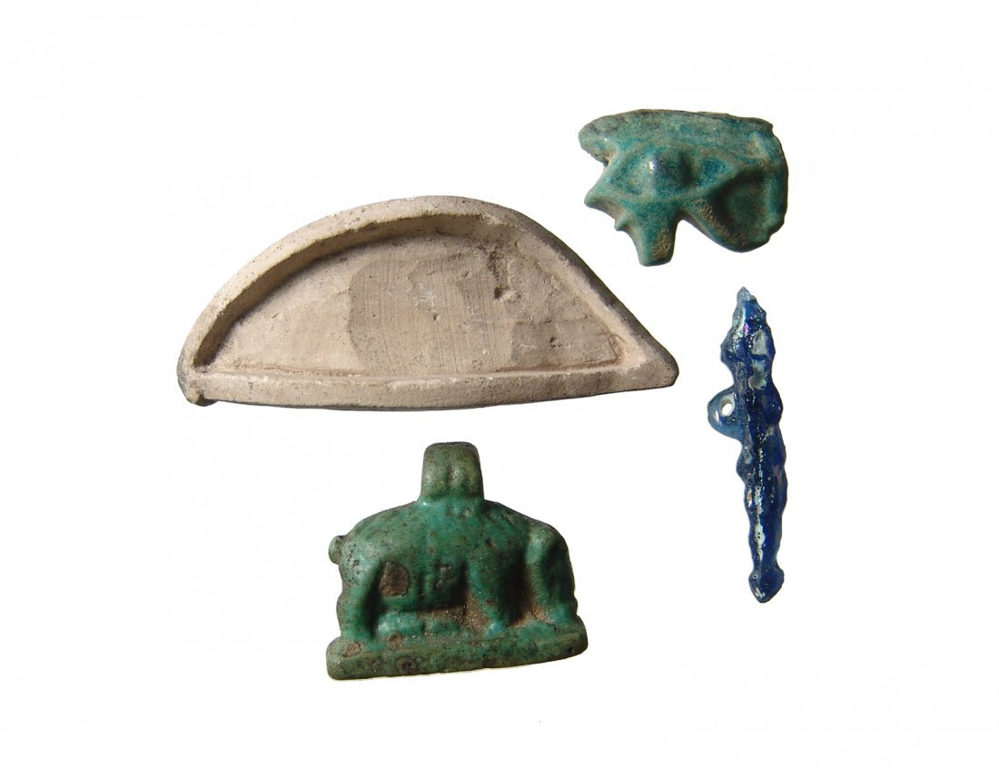 A group of Egyptian amulets and an eye inlay