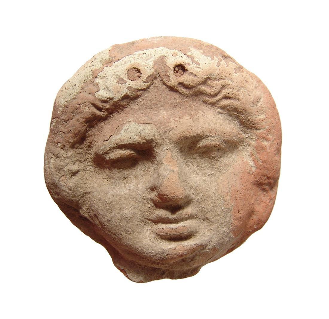 Greek terracotta roundel depicting face of a Gorgon
