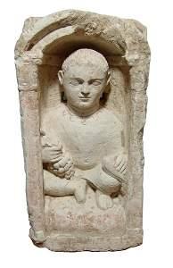 Large Coptic limestone funerary stela depicting a youth