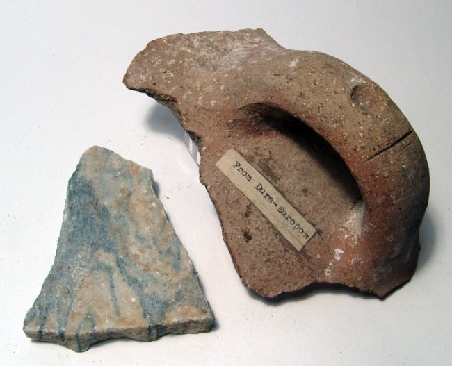 A fragment of Roman marble floor tile and jar handle