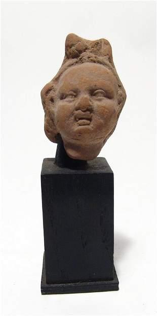 An Egyptian terracotta head of Harpokrates