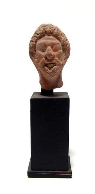 An Egyptian terracotta head of a priest