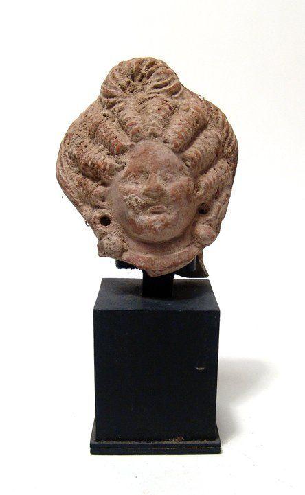 An Egyptian terracotta head of a woman