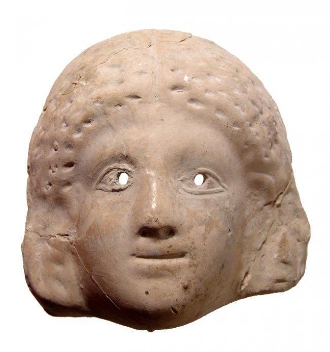 A terracotta Greek mask of a woman