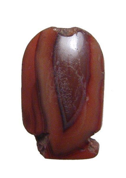 An Egyptian carnelian cartouche-shaped bead