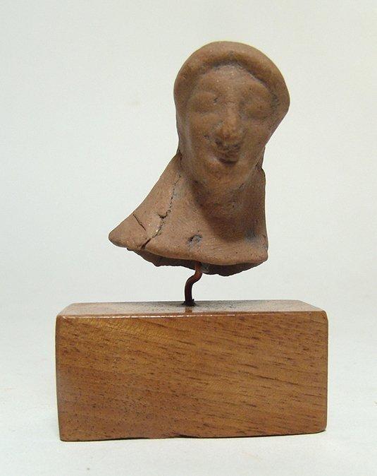 A Greek terracotta bust of a Kore