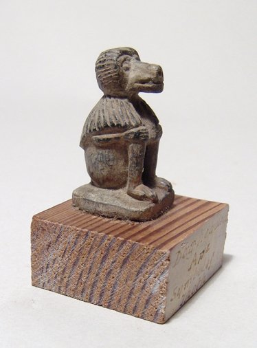 An Egyptian steatite amulet of a seated baboon