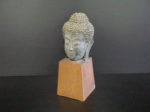 Large Cambodian bronze head on a wooden base.