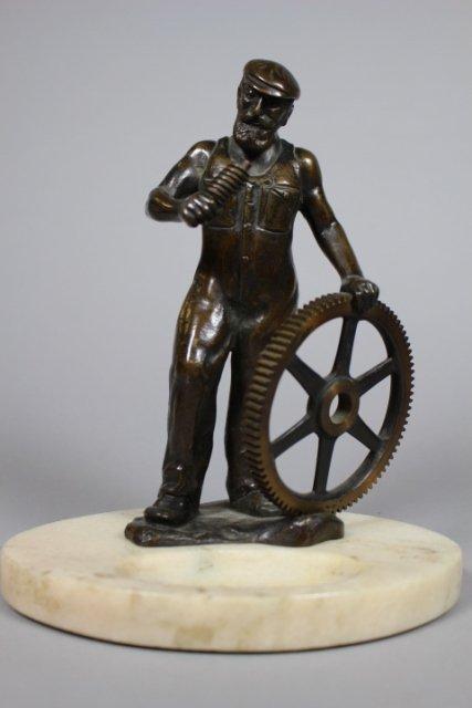 Bronze Statue Of Man With Gear Wheel
