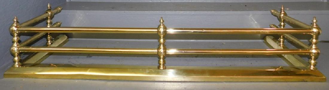 Polished brass tubular fireplace fender.