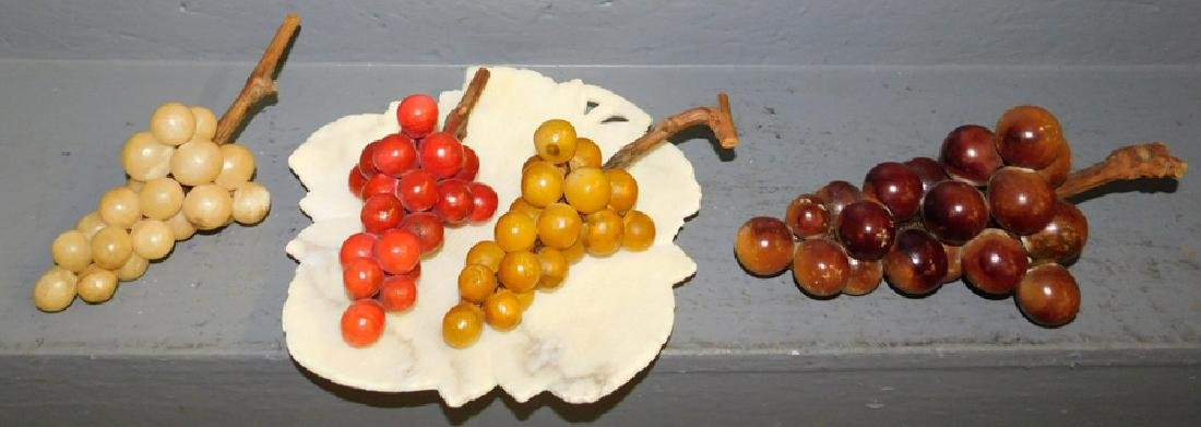 Group of 4 stone grapes clusters on marble plate
