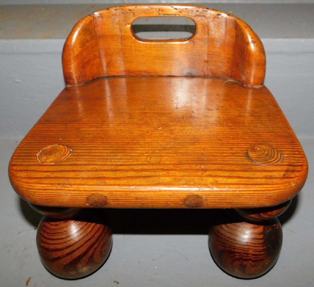 Yellow pine child's stool with carrying handle.