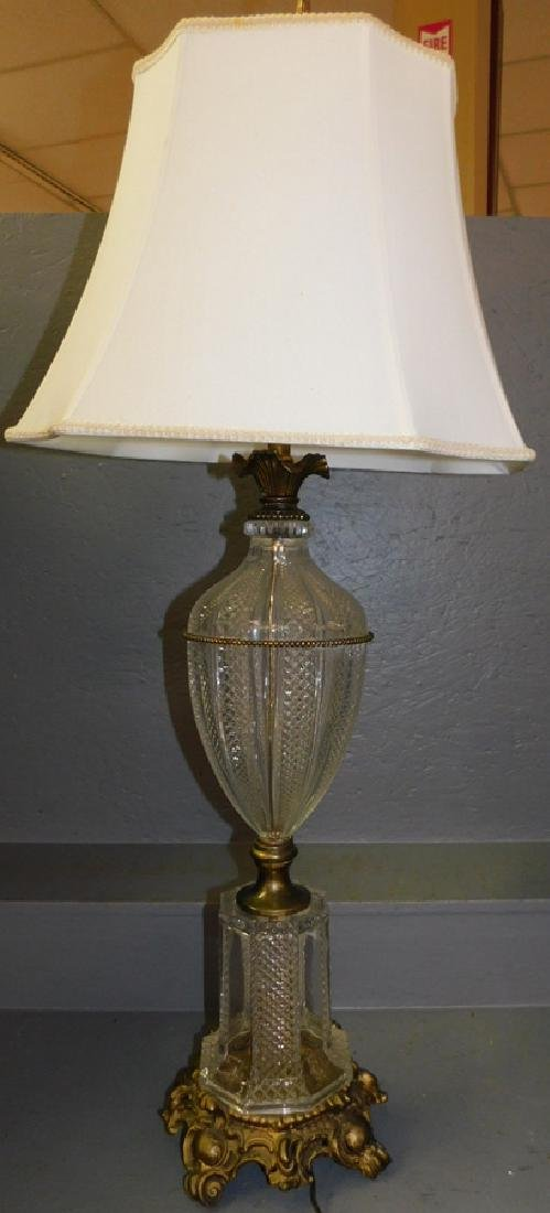 Tall glass pedestal lamp with shade.
