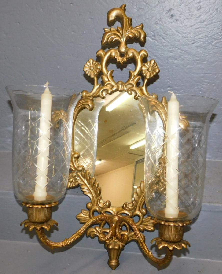 Mirrored brass wall sconce with shades.