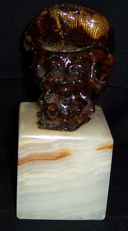 18: Small bust of pipe smoker on marble stand.