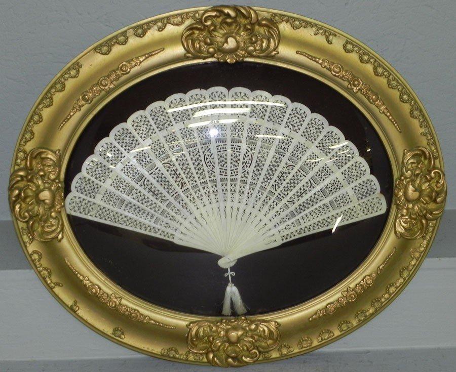 391: Oval framed fan of ivory or celluloid.