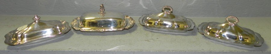 12: (4) silver plate butter dishes.