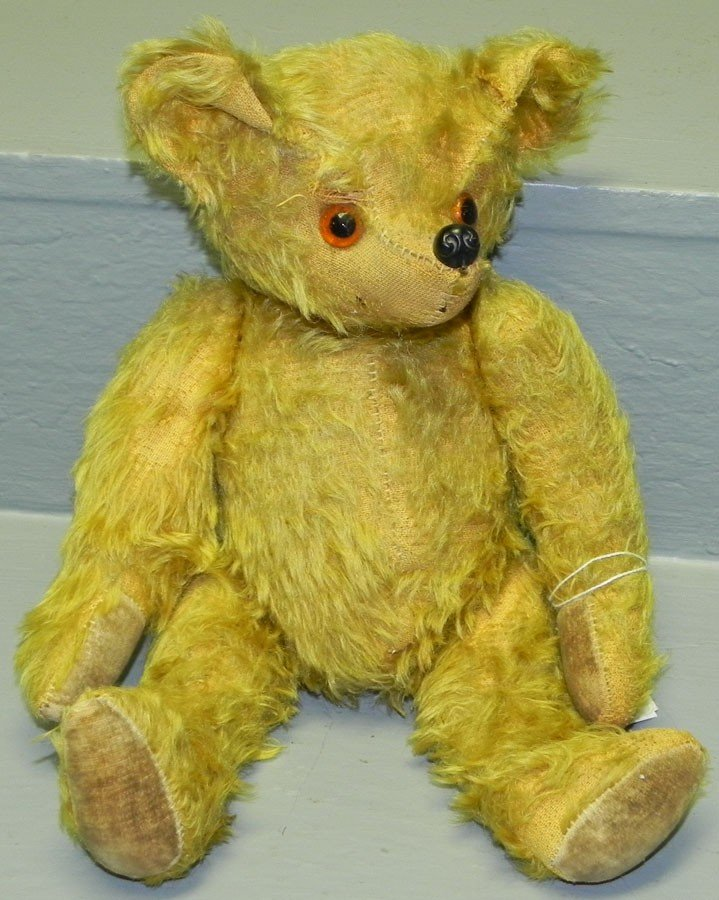 25: Old jointed glass eyed teddy bear.