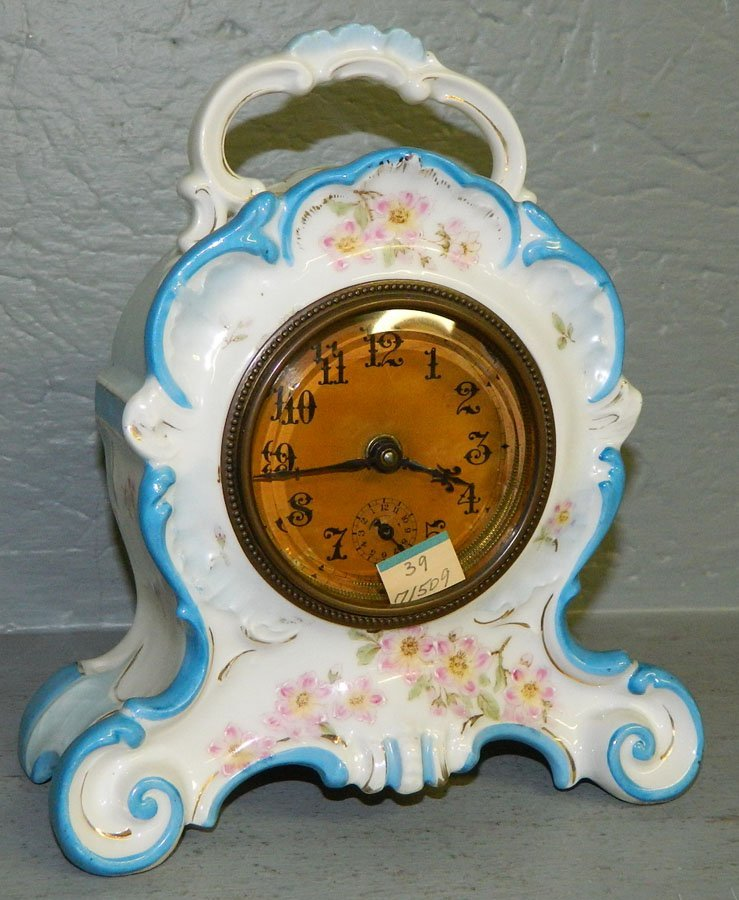 39: White porcelain alarm clock with floral detail.